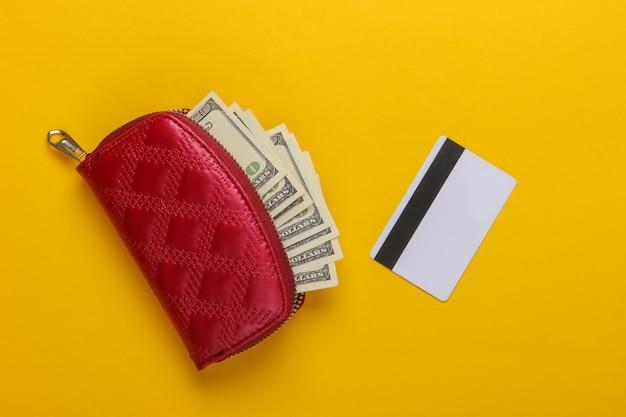 Sac à main rouge avec billets de cent dollars et carte bancaire sur jaune.