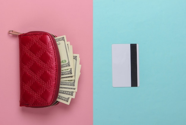 Sac à main rouge avec billets de cent dollars et une carte bancaire sur un pastel bleu-rose.