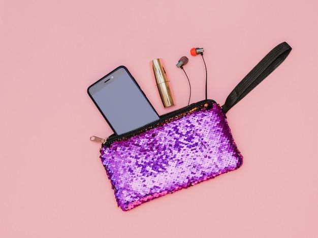 Sac à main violet pour femme avec téléphone rouge à lèvres et casque sur une table rose. couleur pastel. mise à plat.