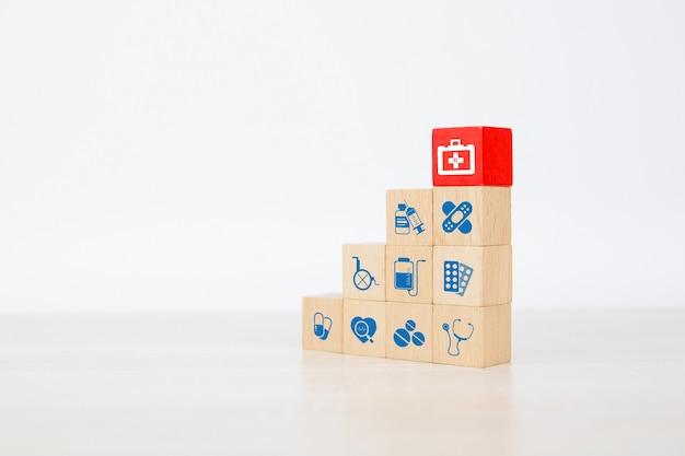 Sac de médecine en gros plan et symbole médical sur la pile de blocs de bois cube.