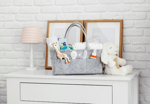Sac de mères avec jouet, couches et accessoires sur blanc