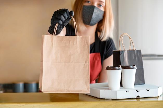 Sac de nourriture, pizza, forfait boisson à emporter en restaurant à emporter. un employé de cuisine passe des commandes en ligne de gants et de masques. sac en papier pour aliments à emporter. confinement de livraison de nourriture sans contact covid 19.