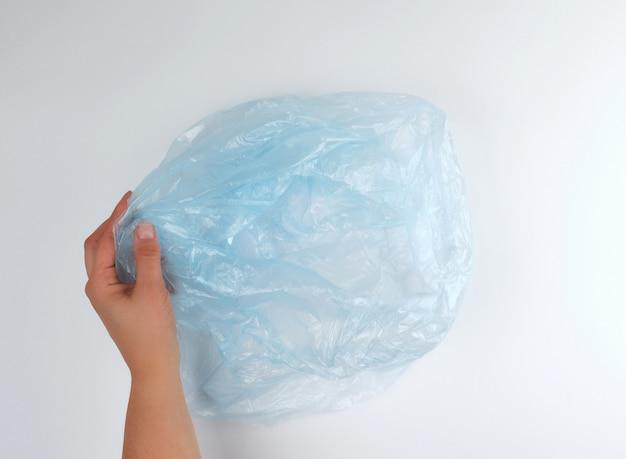 Sac à ordures en plastique bleu dans une main féminine