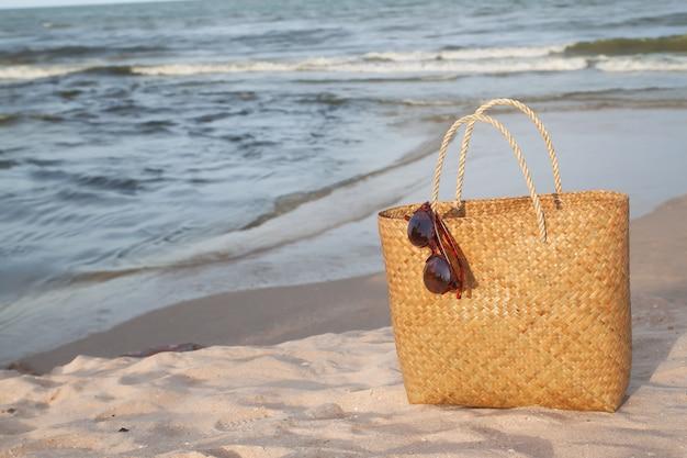 Sac de paille avec des lunettes de soleil sur la plage et la lumière du coucher du soleil