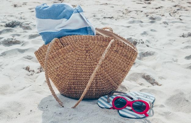 Sac de paille, lunettes de soleil et tongs sur une plage de sable tropicale