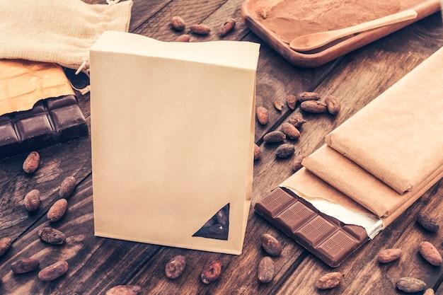 Sac en papier avec des barres de chocolat et des fèves de cacao sur une table en bois