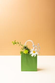 Sac en papier avec de belles fleurs et plantes de jardin d'été sur fond beige