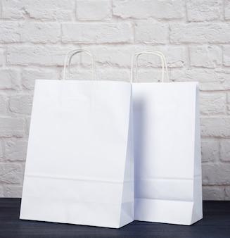 Sac en papier blanc avec poignées sur mur de briques blanches