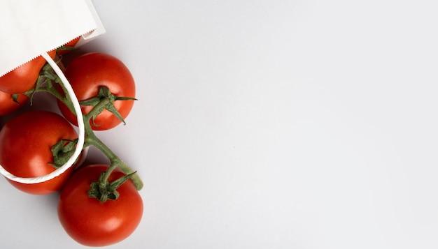 Sac en papier blanc avec des tomates sur fond gris, place pour le texte, vue de dessus.
