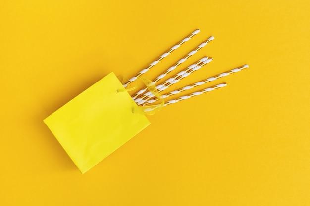 Sac en papier cadeau et pailles avec rayures dorées sur jaune.