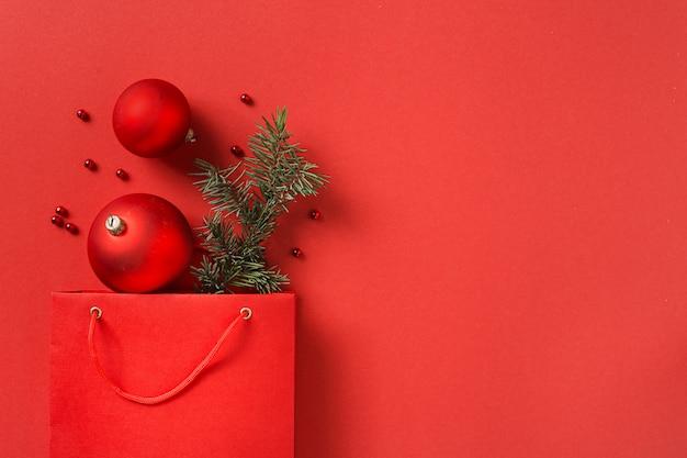 Sac de papier commercial rouge de noël avec décoration sur la vue de dessus espace copie rouge