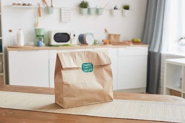 Sac en papier craft sur table en bois dans l'intérieur de la cuisine blanche avec étiquette d'aliments biologiques, service de livraison de nourriture
