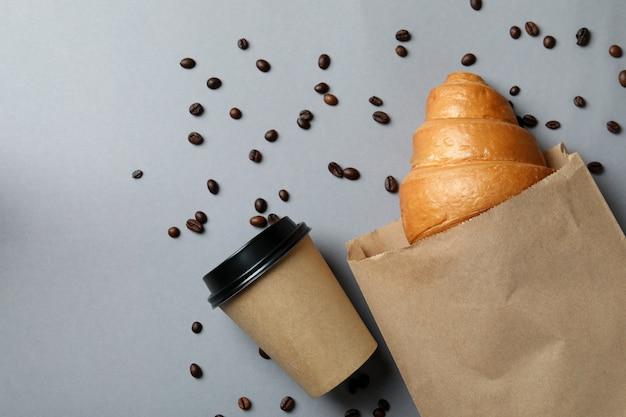 Sac en papier avec croissant, tasse en papier et graines de café sur fond gris