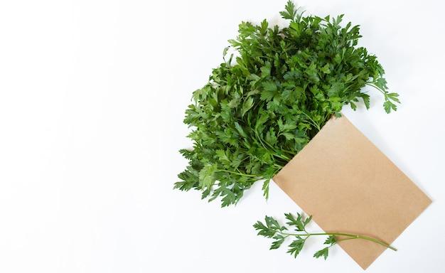 Sac en papier avec du persil biologique frais isolé sur fond blanc, vue du dessus