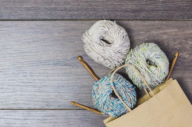 Sac en papier et fournitures de tricot sur table en bois