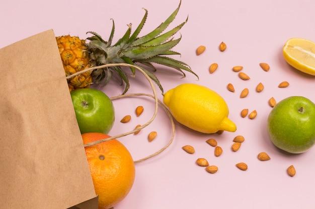 Sac en papier avec des fruits sur fond rose pomme citron pamplemousse ananas noix.