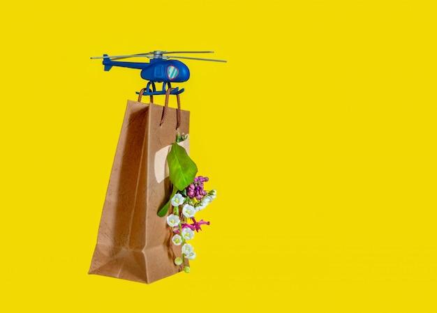 Sac en papier jaune fleur jouethélicoptère mouche livraison fond bleu.