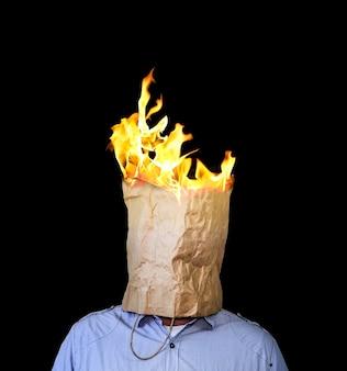 Un sac en papier kraft brûlant est sur la tête de l'homme. concept effrayant et d'horreur.
