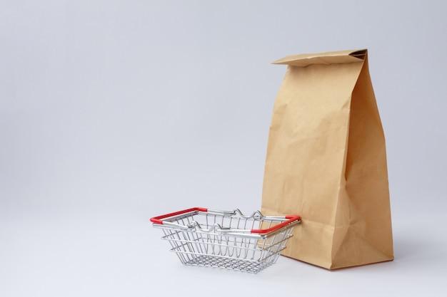 Sac en papier kraft brun pour faire du shopping sur une surface blanche et un petit panier d'épicerie