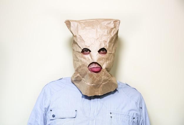 Le sac en papier kraft est sur la tête de l'homme. trous pour les yeux. drôle d'idée. guy montre sa langue.