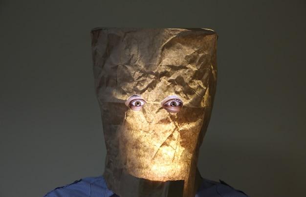 Le sac en papier kraft est sur la tête de l'homme. trous pour les yeux. drôle d'idée.