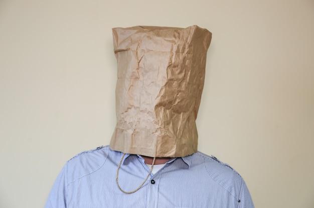 Le sac en papier kraft est sur la tête de l'homme.