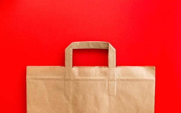 Sac en papier kraft vide sur fond rouge, composition à plat, vue de dessus, maquette d'emballage de recyclage