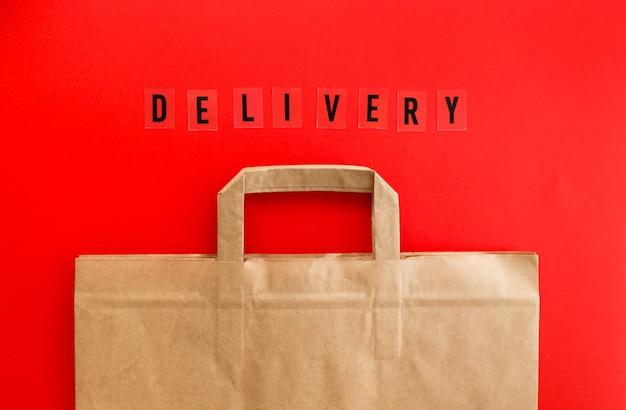 Sac en papier kraft vide avec mot livraison sur fond rouge, composition à plat, vue de dessus, maquette d'emballage de recyclage