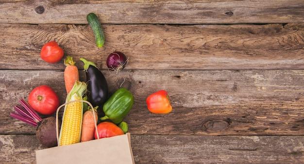 Un sac en papier avec des légumes éparpillés sur un fond en bois. espace pour le texte