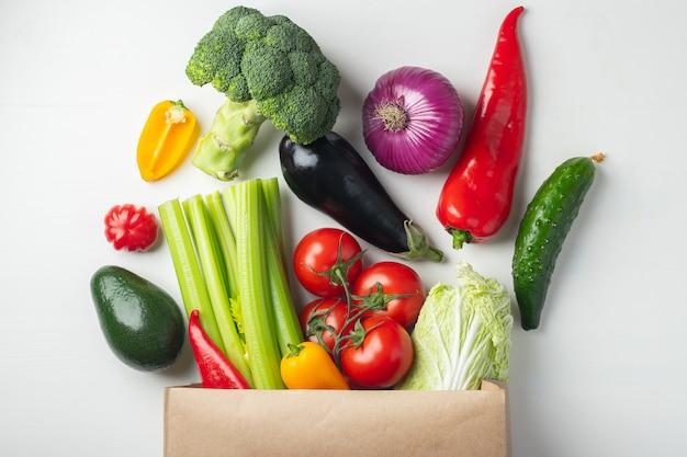 Sac en papier avec des légumes sur fond blanc.