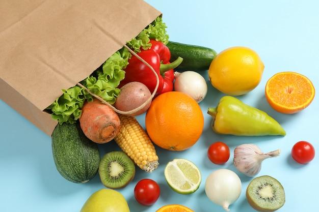 Sac en papier, légumes et fruits sur un espace bleu pour le texte
