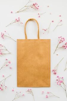 Sac en papier parmi les fleurs tendres