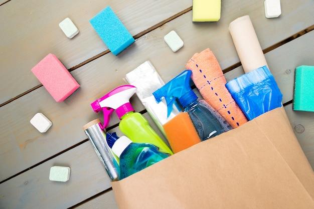 Sac en papier plein de différents produits de nettoyage de maison sur table en bois.