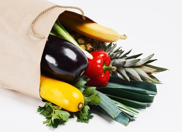 Sac en papier plein de légumes de saison