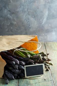 Sac en papier avec des pointes d'asperges violettes naturelles biologiques fraîchement cueillies sur un fond en bois.