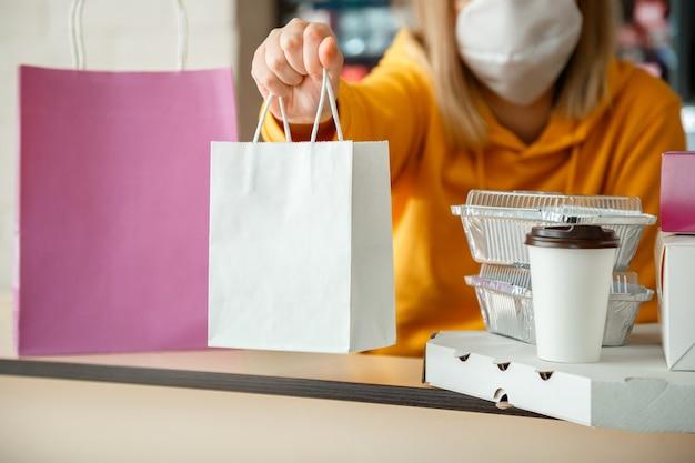 Sac en papier pour aliments à emporter. le sac de la boîte de nourriture boit du café pour aller au restaurant à emporter. un employé de cuisine passe des commandes en ligne de gants et de masques. livraison de nourriture sans contact pendant le confinement covid 19.