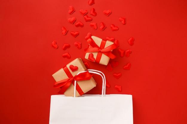 Sac en papier shopping blanc avec des confettis coeurs rouges et des cadeaux sur le rouge. saint valentin . vue de dessus, pose à plat