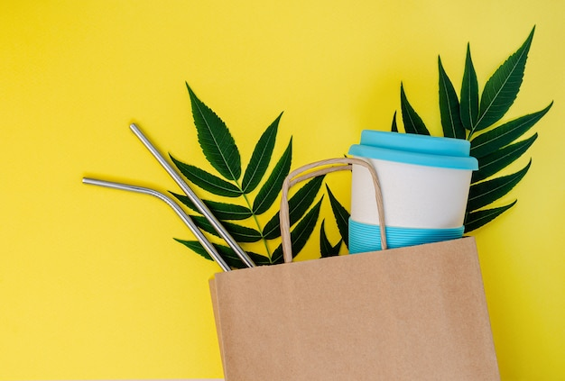 Sac en papier avec tasse en bambou et pailles réutilisables sur fond jaune.