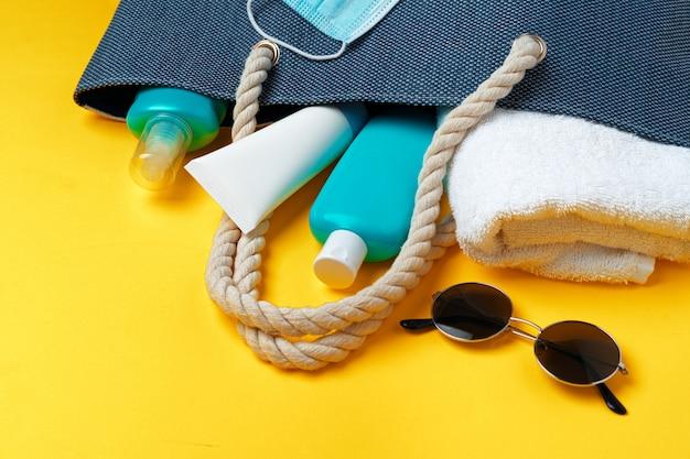 Sac de plage bleu avec accessoires de plage et masque de protection sur fond jaune