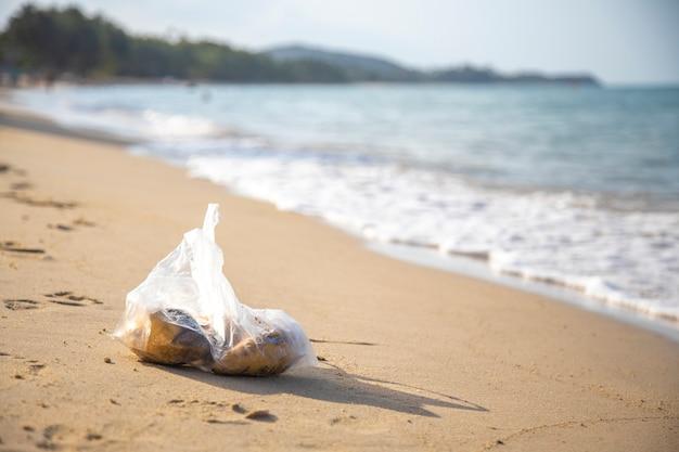 Sac en plastique allongé sur une plage tropicale de sable. pollution environnementale. poubelle dans la mer