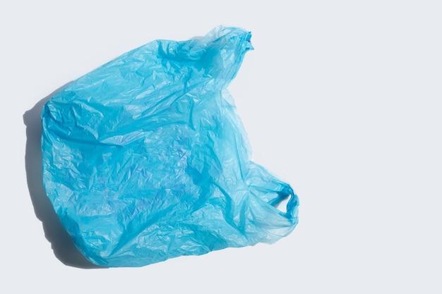 Sac en plastique bleu sur une surface blanche.