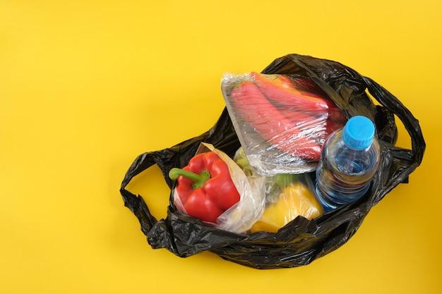 Sac en plastique noir avec des produits d'épicerie sur l'espace de copie de fond jaune dites non au concept en plastique