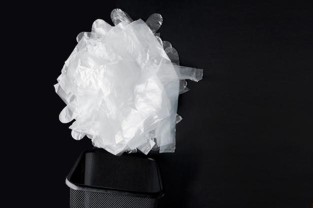 Sac en plastique avec poignées, gants dans la poubelle sur fond noir