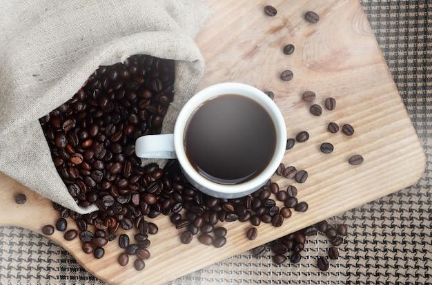 Un sac plein de grains de café brun et une tasse blanche de café chaud repose sur une surface en bois