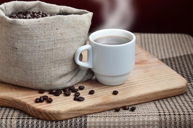 Un sac plein de grains de café brun et une tasse blanche de café chaud