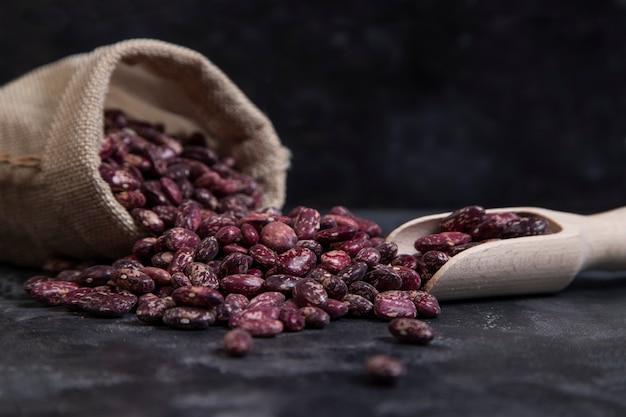 Un sac plein de grains crus de haricots secs placés sur fond noir