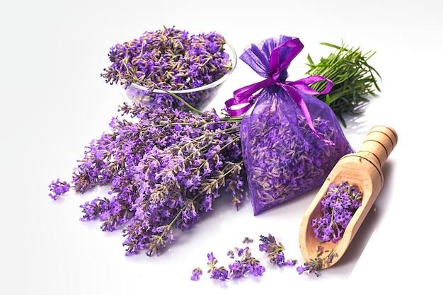 Sac ou pochette parfumée avec des fleurs de lavande sur fond blanc. brins de lavande près du sachet de lavande.