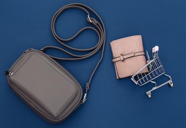 Sac et portefeuille en cuir à la mode avec chariot sur fond bleu classique. notion de magasinage. couleur 2020. vue de dessus. mise à plat