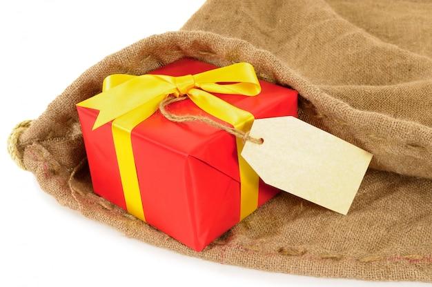 Sac postal avec cadeau rouge et étiquette.