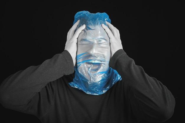 Sac poubelle bleu sur la tête de l'homme. sac de sortie pour suicide. concept d'auto-asphyxie. sac de suicide sur la tête de l'homme. essoufflement, manque d'air. fond noir.